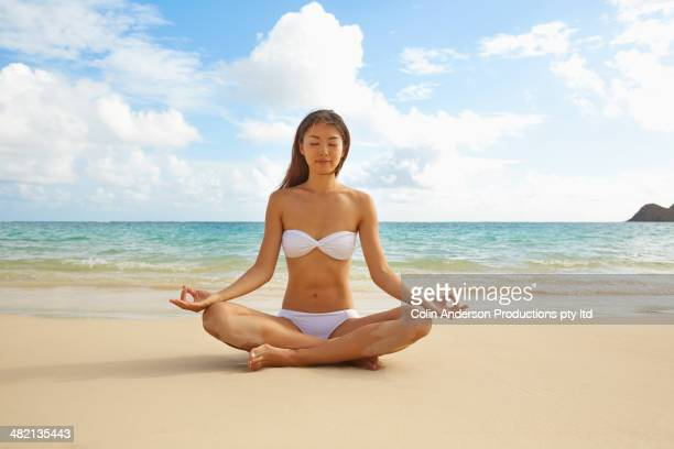 Japanese woman meditating on beach