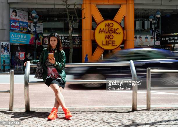 Japanese woman Noemi poses for a picture as she watches on her smartphone the live stream of One World Together At Home presented by Global Citizen...