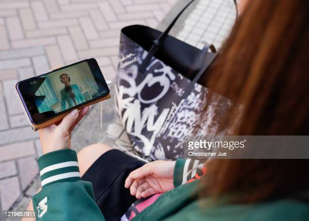 Japanese woman Noemi poses for a picture as she watches on her smartphone the live stream performance of Celine Dion during the One World Together At...