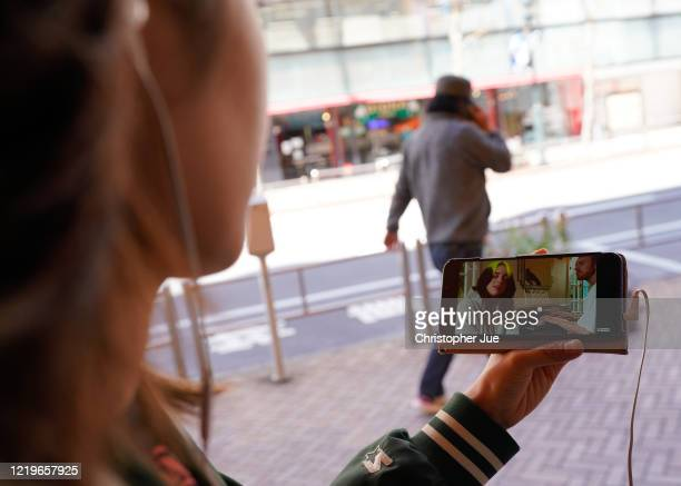 Japanese woman Noemi poses for a picture as she watches on her smartphone the live stream performance of Billie Eilish and Finneas O'Connell during...