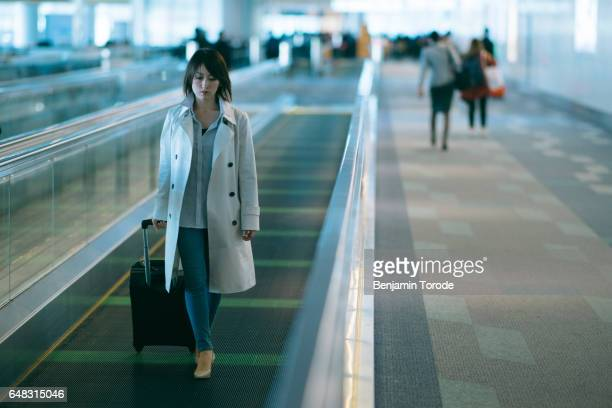 Japanese woman on moving walkway in airport terminal pulling luggage