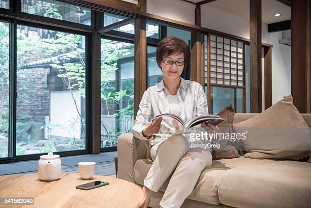 Japanese woman on sofa reading magazine