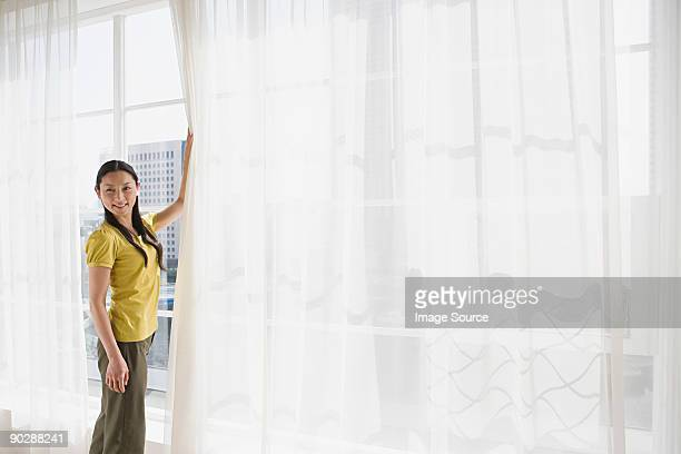Japanese woman opening net curtains