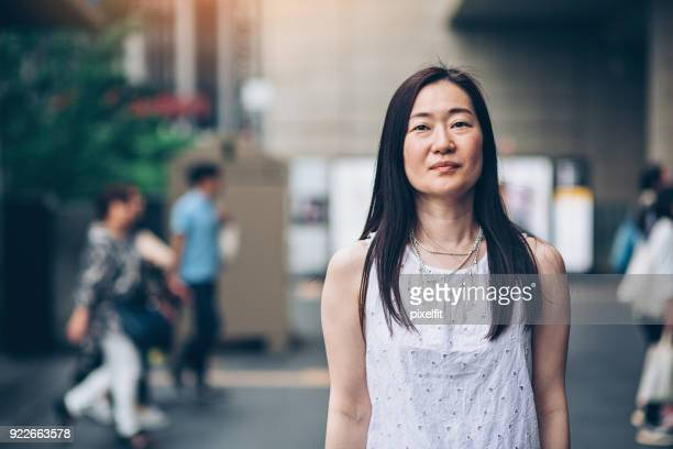 japanese woman outdoors in the city - looking at camera stock pictures, royalty-free photos & images