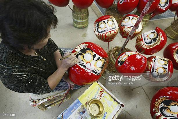 Japanese woman paints a good luck charm called Daruma ahead of the major national elections today November 9 2003 in Takasaki Japan The Daruma is...