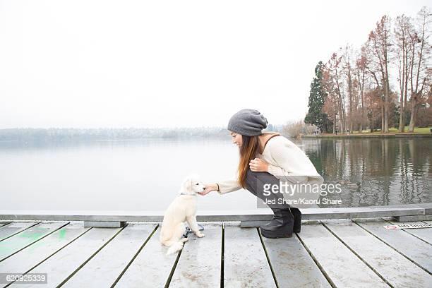 Japanese woman petting dog near lake