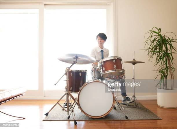 Japanese woman playing drums in living room