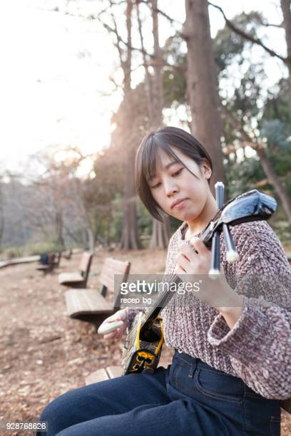 japanese woman playing japanese musical enstrument - shamisen stock photos and pictures