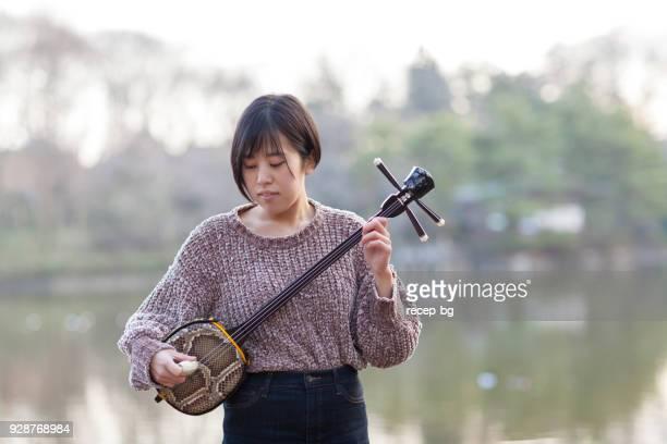 japanese woman playing japanese musical enstrument - vangen imagens e fotografias de stock