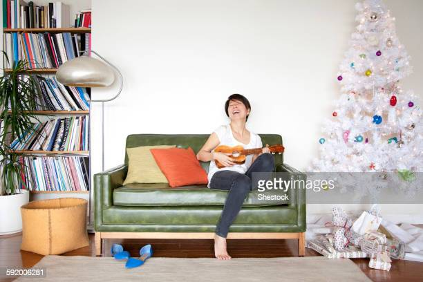 Japanese woman playing ukulele near Christmas tree