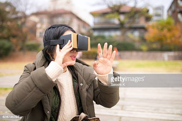 Japanese woman playing with vitural reality simulator