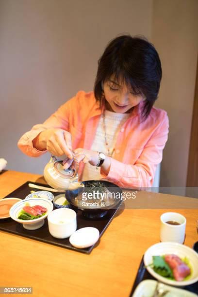 お茶漬けのご飯に緑茶を注いで日本女性