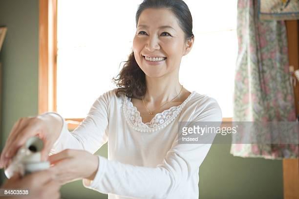 Japanese woman pouring sake, smiling