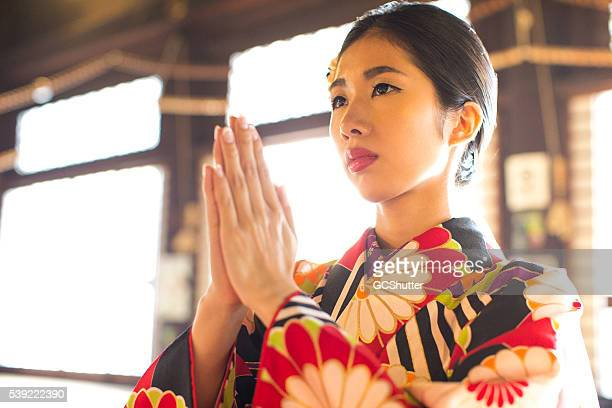 Japanese woman praying at a temple