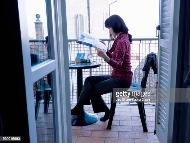 Japanese woman reading map on balcony