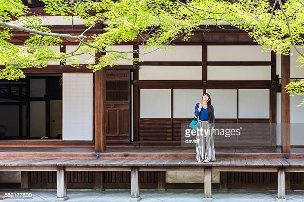 japanese woman relaxing in the grounds of buddhist temple - shrine stock pictures, royalty-free photos & images