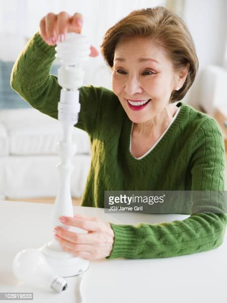 Japanese woman replacing energy efficient light bulb