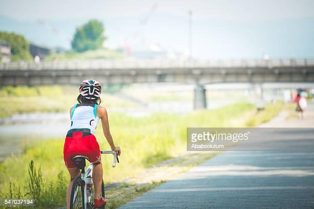 Japanese Woman Riding a Bike by Kamo River, Kyoto, Japan
