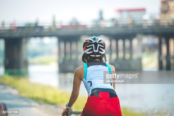 japanese woman riding a bike by kamo river, kyoto, japan - fluss kamo stock-fotos und bilder