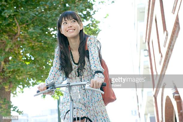 Japanese woman riding bicycle on street