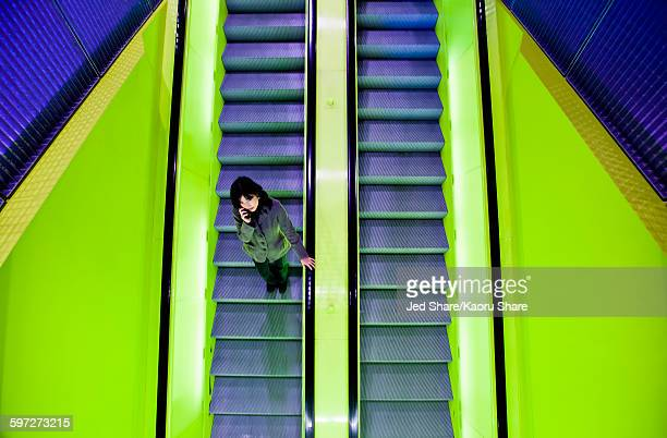 Japanese woman riding escalator