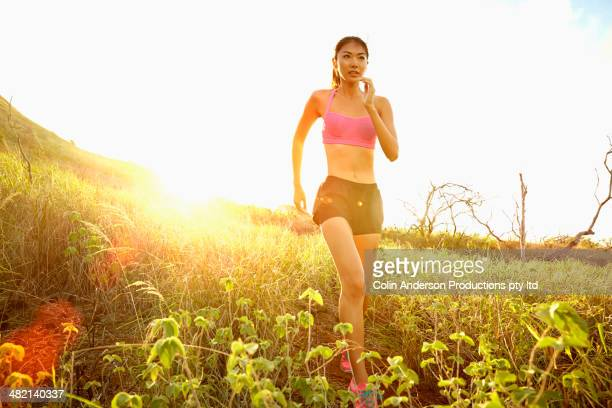 Japanese woman running in rural field