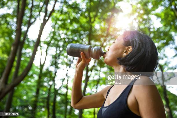 japanese woman running in the forest above kyoto - energy drink stock pictures, royalty-free photos & images