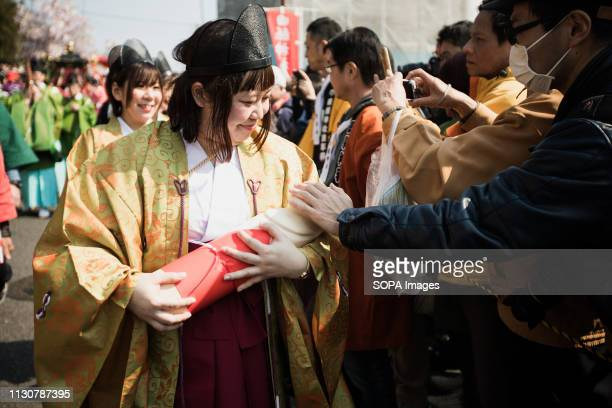 Japanese woman seen holding a replica of a phallus during the festival Honen festival is a traditional famous festival in Tagata Jinja Shrine komaki...
