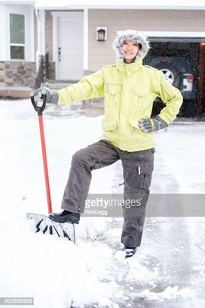 japanese woman shoveling snow - parka coat stock photos and pictures
