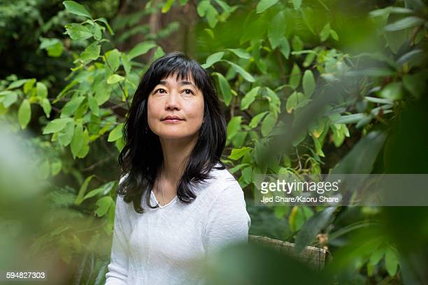 Japanese woman sitting in garden