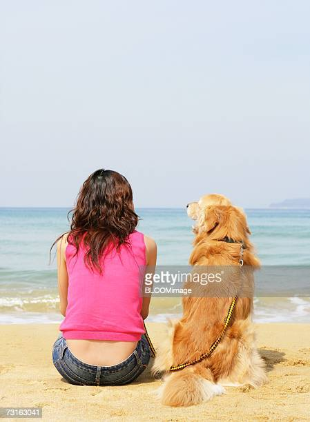 Japanese woman sitting with dog on the beach