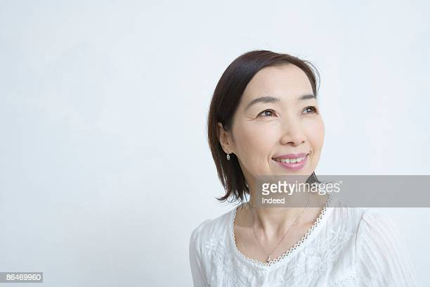 Japanese woman smiling, looking away