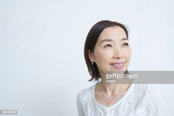 Japanese woman smiling, looking away