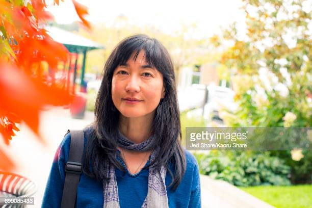 Japanese woman smiling near autumn leaves