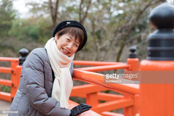 Japanese woman smiling on a red bridge