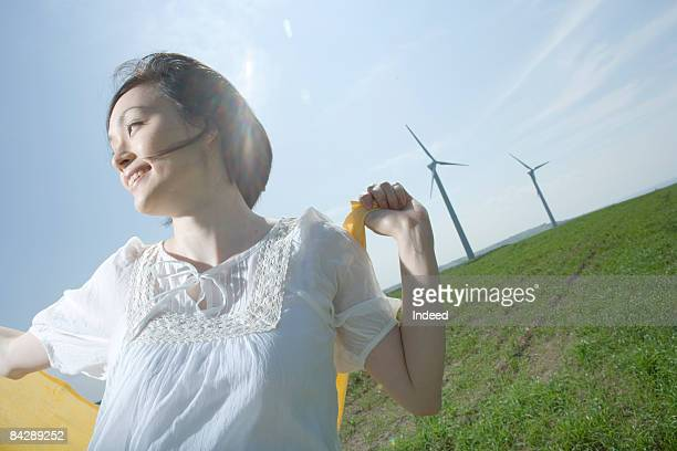 Japanese woman smiling on grass, looking away