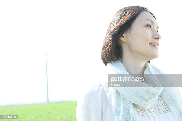 japanese woman smiling on grass, portrait - 30代 ストックフォトと画像