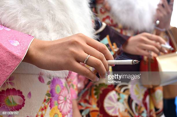 A Japanese woman smokes a cigarette at a ceremony celebrating the Coming of Age Day at an amusement park in Tokyo January 9 2017 Youths across Japan...