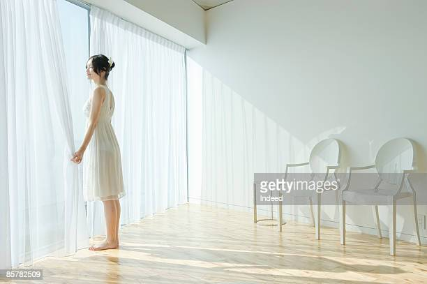 Japanese woman standing and looking through window