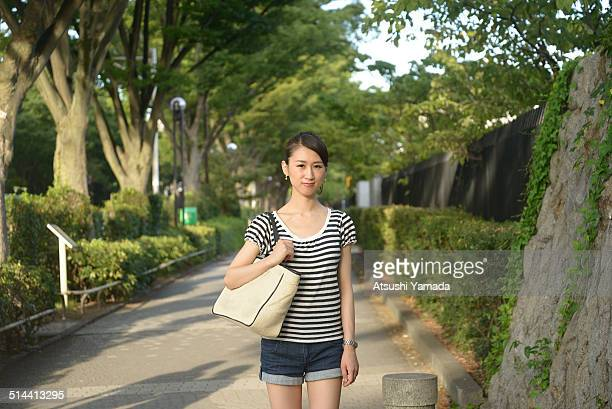 Japanese woman standing beside park,smiling