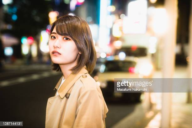 japanese woman standing in glow light of night street - one young woman only stock pictures, royalty-free photos & images