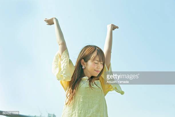 Japanese woman stretching with sky background