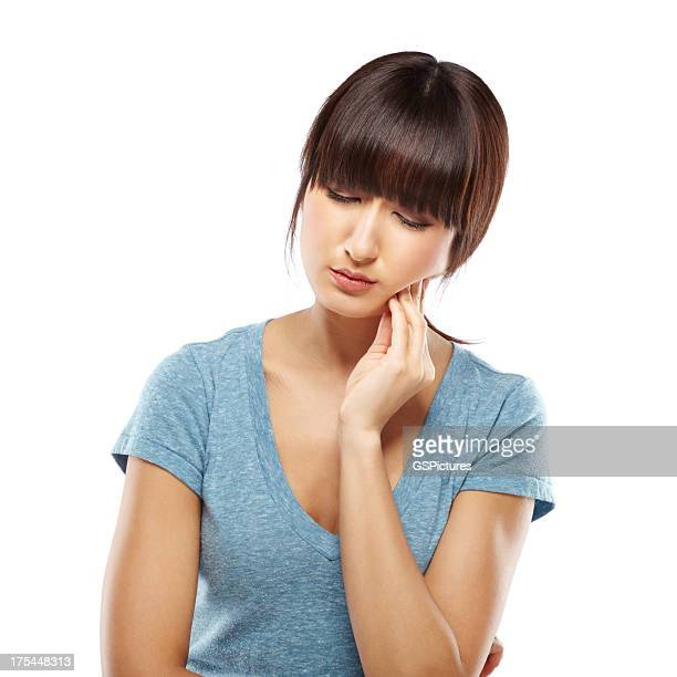 Japanese woman suffering from toothache holding a hand on jaw