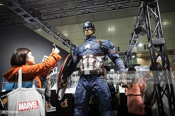 A Japanese woman takes pictures of a Captain America figure during Tokyo Comic Con in Chiba in the suburb of Tokyo on December 2 2016 / AFP / Behrouz...