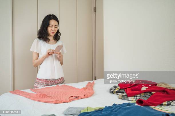 japanese woman taking pictures of used clothes for online flea market - フリーマーケット ストックフォトと画像