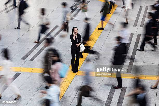 japanese woman talking on the mobile phone surrounded by commuters - mensen op de achtergrond stockfoto's en -beelden