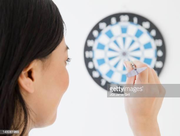 japanese woman throwing dart at dartboard - darts stock-fotos und bilder