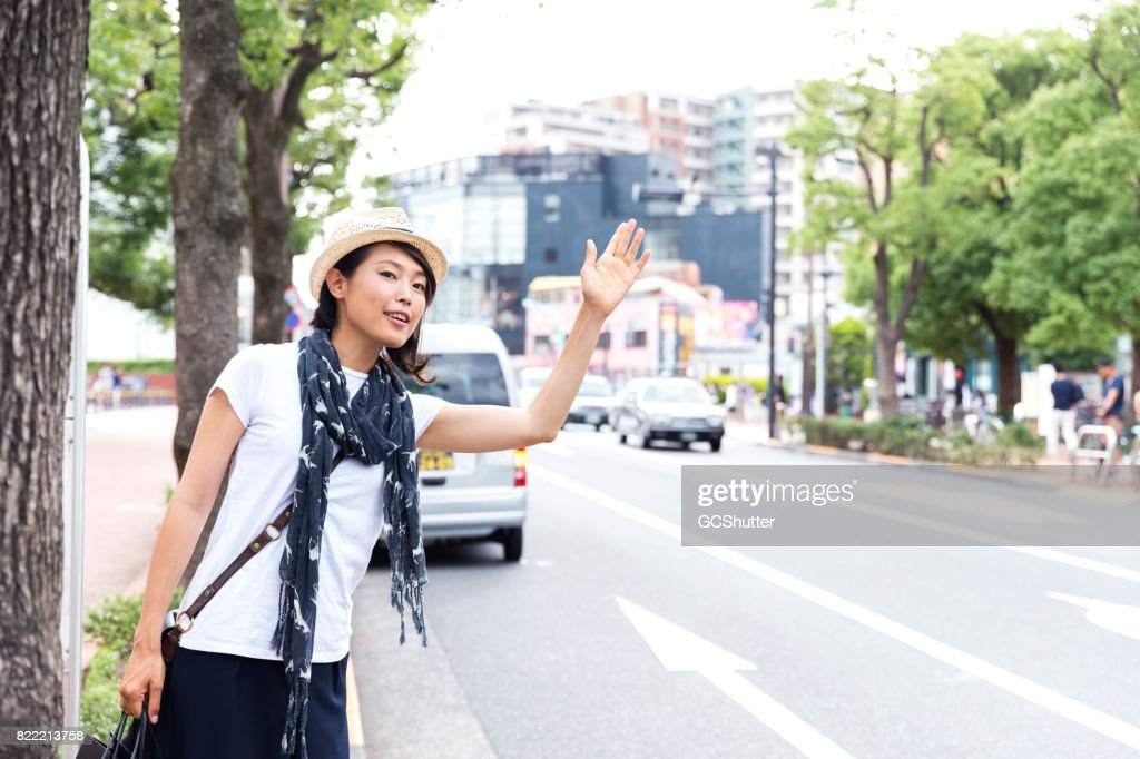 Japanese woman trying to hail a taxi : Stock Photo