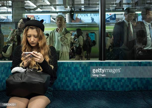 Japanese woman uses her phone on an empty Tokyo JR Yamanote line train after work