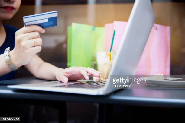Japanese woman using her credit card to do online shopping